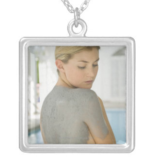 Woman getting spa skin treatment square pendant necklace