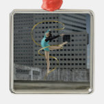 Woman gymnast outdoors on rooftop jumping in air ornaments