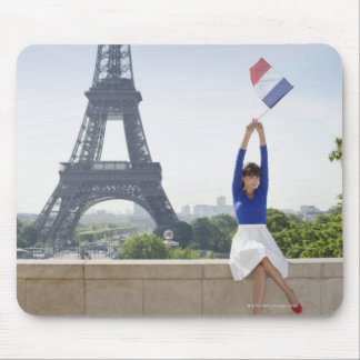 Woman holding a French flag sitting on a stone Mousepads