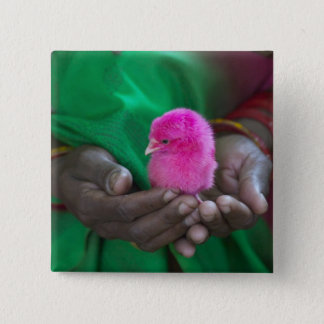 Woman holding a little chick painted with holy button