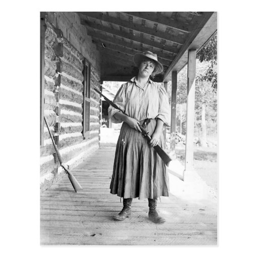 Woman holding a rifle on a porch postcard