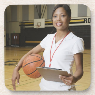 Woman holding basketball and clipbpard, smiling, drink coaster