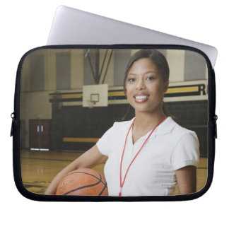 Woman holding basketball and clipbpard, smiling, laptop computer sleeves