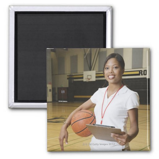 Woman holding basketball and clipbpard, smiling, magnet