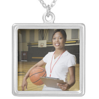 Woman holding basketball and clipbpard, smiling, custom necklace