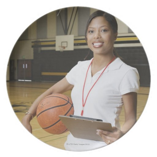 Woman holding basketball and clipbpard, smiling, plate