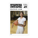 Woman holding basketball and clipbpard, smiling, stamp