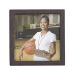 Woman holding basketball and clipbpard, smiling, premium jewelry box