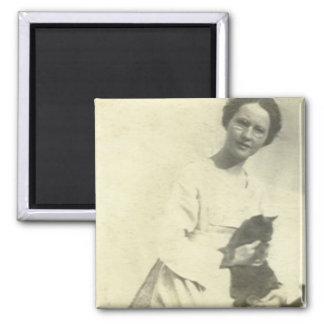 Woman holding cat on lap sitting on fence fridge magnet