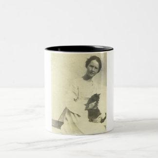 Woman holding cat on lap sitting on fence mugs