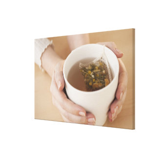 Woman holding cup with chamomile tea canvas print