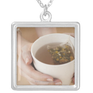 Woman holding cup with chamomile tea custom jewelry