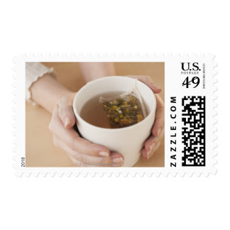 Woman holding cup with chamomile tea postage stamp