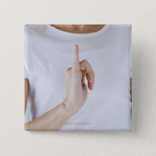 Woman holding hand up with outstretched small pinback button