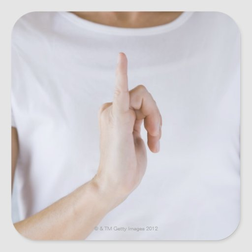 Woman holding hand up with outstretched small square sticker