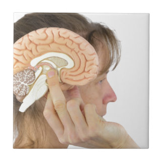 Woman holding hemisphere model  against head ceramic tile