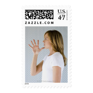 Woman holding open hand to chin. postage