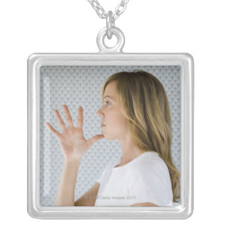 Woman holding open hand to chin. silver plated necklace