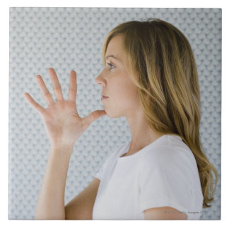 Woman holding open hand to chin. tile