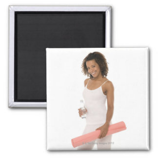 Woman holding water bottle and exercise mat magnet