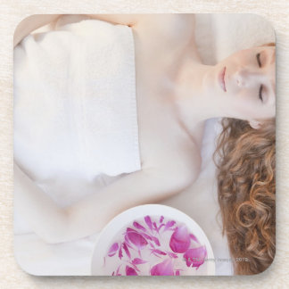 Woman in bed beverage coasters
