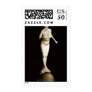 Woman in mermaid costume balancing on ball postage