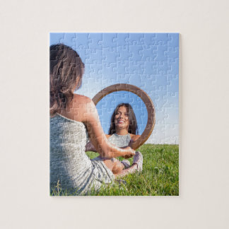 Woman in nature viewing her mirror image jigsaw puzzle