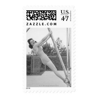 Woman in swimsuit hanging from wooden postage