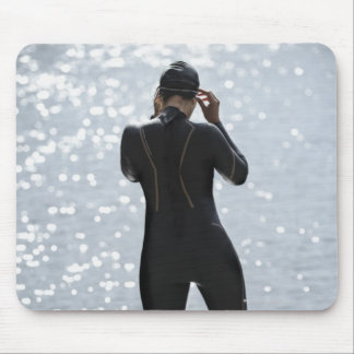 Woman in wetsuit standing on rock mouse pad