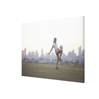 Woman kneeing soccer ball in urban park gallery wrapped canvas