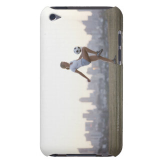 Woman kneeing soccer ball in urban park iPod touch cover