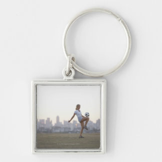 Woman kneeing soccer ball in urban park key chains