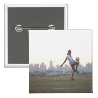 Woman kneeing soccer ball in urban park pinback button