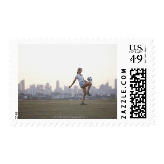 Woman kneeing soccer ball in urban park postage