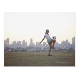 Woman kneeing soccer ball in urban park postcard