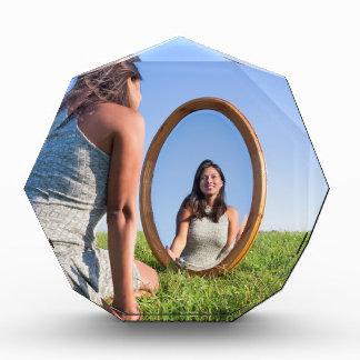 Woman kneeling on grass looking at mirror image acrylic award