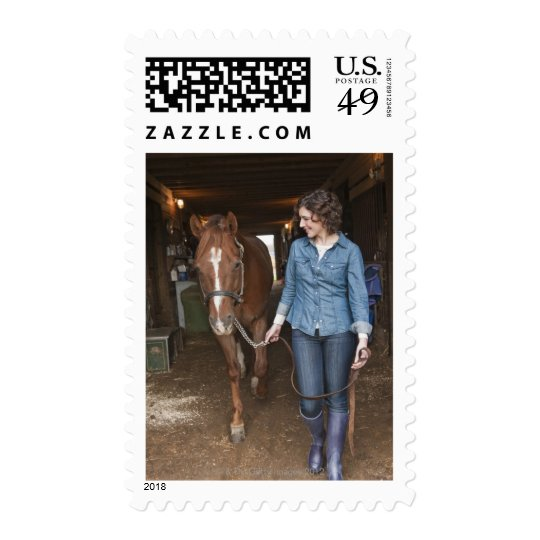 Woman leading horse postage