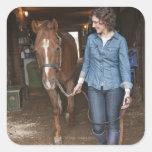Woman leading horse square sticker