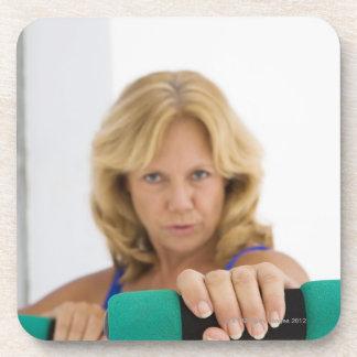 Woman lifting dumbbells drink coaster