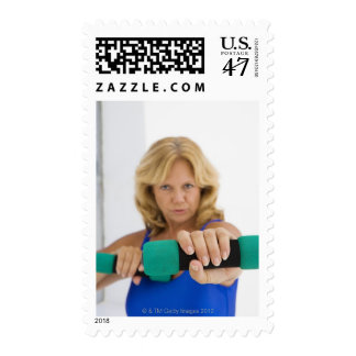 Woman lifting dumbbells postage