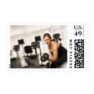 Woman lifting weights in gym 2 postage