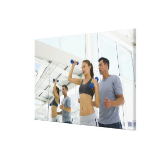 Woman lifting weights with trainer canvas print