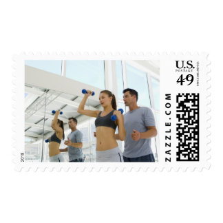 Woman lifting weights with trainer stamp