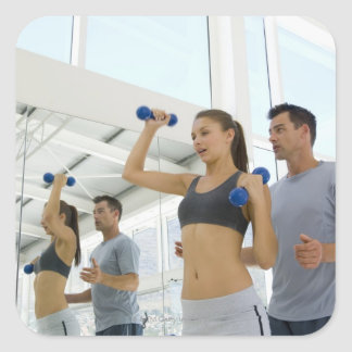 Woman lifting weights with trainer square sticker