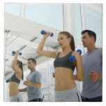 Woman lifting weights with trainer tile