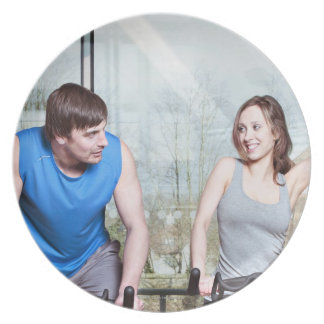 Woman on exercise bike triumphing over man dinner plates