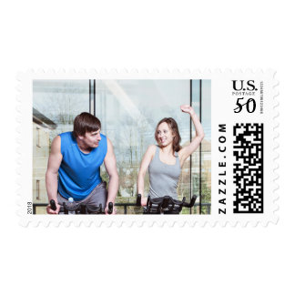 Woman on exercise bike triumphing over man postage