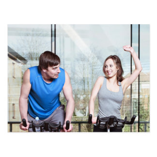 Woman on exercise bike triumphing over man postcard