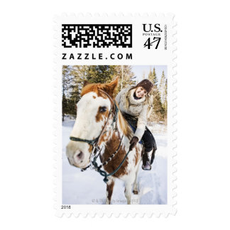 Woman on horse outdoors during winter postage