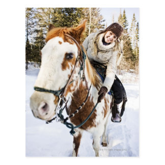 Woman on horse outdoors during winter post card
